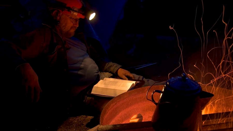 Man reading a book with headlamp